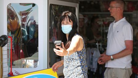 A woman wearing a face mask at a tourist kiosk in Bridlington, East Yorkshire on Thursday. Angus Wil