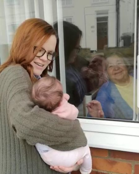 Maeve Algar from Halesworth meeting her grandmother for the first time through a window. Picture: HO