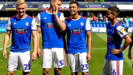 Town's young midfield trio Flynn Downes, Andre Dozzell and Tristan Nydam pictured with Luke Woolfend
