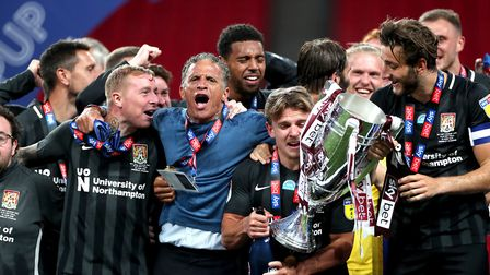Northampton Town players and manager Keith Curle lift the trophy as they celebrate promotion to Leag
