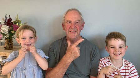 John using Makaton alongside his grandchildren Betsy and Alfie. John is signing 'fun', Betsy is sign