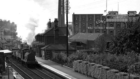 A steam locomotive pulling trucks through Mistley station in the 1930s. The Edme Maltings are on the