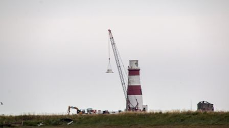 Teams work to remove the top of the lighthouse Picture: CARL HUMPHREY