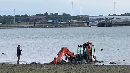 Onlookers watched as the digger tried to get out of the mud Picture: SAMANTHA BATEMAN