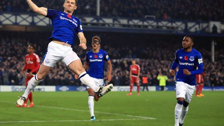 Leighton Baines, left, celebrates one of his goals for Everton - the veteran defender has retired at