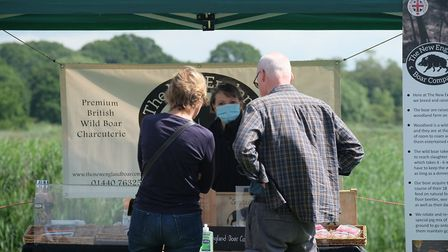 Visitors browsing goods from The New England Boar Company at the Snape Maltings Farmers Market Pictu