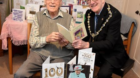 Cyril Doy showing a book of his poetry to Mayor of Southwold Ian Bradbury on his 100th birthday. Pic