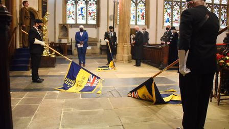 The standards are lowered as the Last Post is played at the County of Suffolk VJ Service of Remembra
