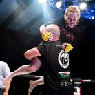 Cory McKenna is held aloft by coach Jack Mason after her win at Cage Warriors 105. Picture: BRETT KI