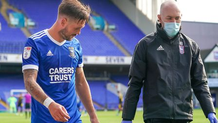 Luke Chambers walks from the pitch with head physio Matt Byard after suffering what appeared to be c
