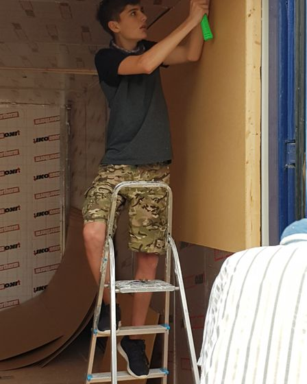 Jadon Leathers is helping to covert a former container into a food bank at red Lodge Litghwave Cafe.