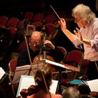 Christopher Green conducts an orchestral rehearsal before lockdown. Prof Green is one of the archite