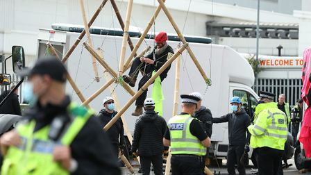 One of the protesters climbs down from the bamboo lock-ons they are using to block the road outside