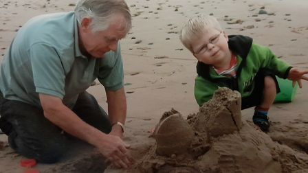 Kenny Scarff sadly died aged 76. He is pictured here building sand castles with his grandson Ben. Pi