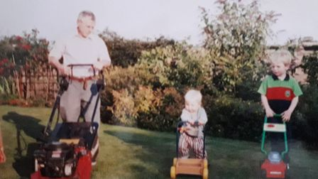 Kenny Scarff teaching two of his grandsons how to mow the lawn. Picture: SCARFF FAMILY