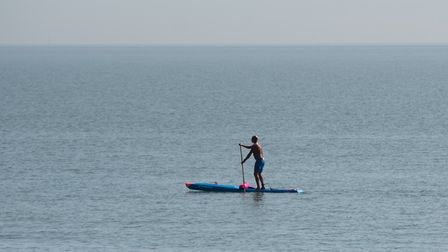 A paddle boarder enjoys the calm sea Picture: SARAH LUCY BROWN