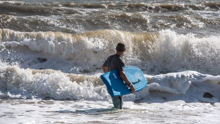 A body boarder heading out into the waves in Southwold Picture: SARAH LUCY BROWN