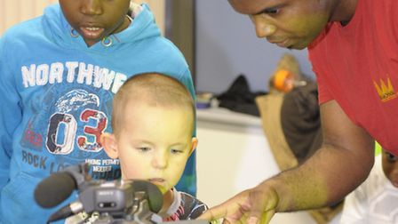 Wayne Saunders shows Billy, five, how to use a video camera. Donell, eight years old, looks at a re