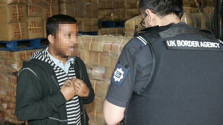 A worker is questioned by a Border Agency officer.