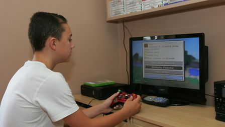 Tracey's son Sid stays inside now playing on his XBox because playing outside is banned