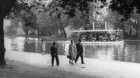 View through trees, across Barking Park's boating lake, with the steam boat Phoenix II on the water