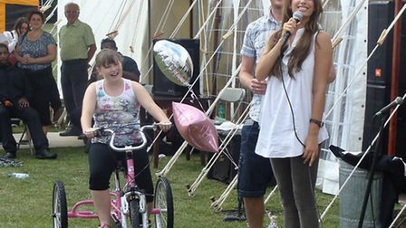 Mollie-Louise Glover (left) is delighted to be awarded her tricycle by singer and presenter Stacey S