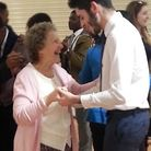 Student George Aguis dancing with an elderly lady