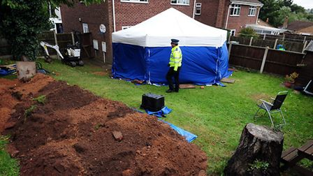 Police in the garden of a house in Blenheim Close, Forest Town, near Mansfield, where the remains of
