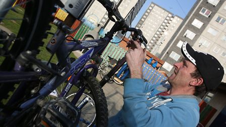 Volunteer Chris Rixon fixing a bike as part of a local organisation taking recycled bikes from the G