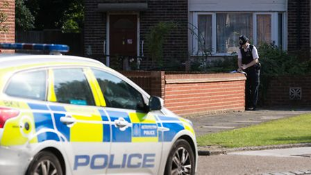 A police officer takes notes outside the house in Wykeham Green where a murder investigation has bee