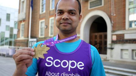 Syed, 37, with a medal he won completing his 100k push in one year