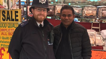 PC Paul Andrews with Ahmed Ejaz at his stall in Ripple Road at Barking market. Picture: MPS Barking