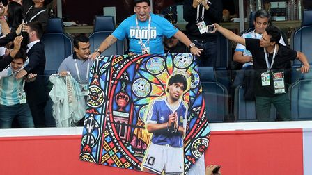 Diego Maradona holds a banner of himself in the stands before the FIFA World Cup Group D match at Sa
