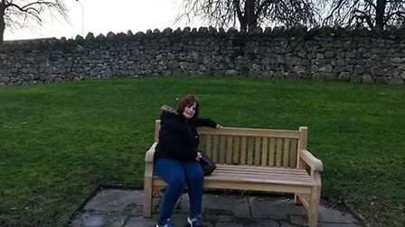 Michelle Grant on a bench dedicated to her father, John Bloom. With no record of the bench being rem