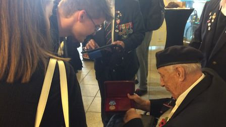 Veteran Les Underwood shows his medals to a pupil commemorative event hosted by Sydney Russell Schoo