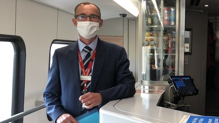 Senior Greater Anglia manager Andrew Goodrum shows off a cafe-bar on a new Intercity train from the