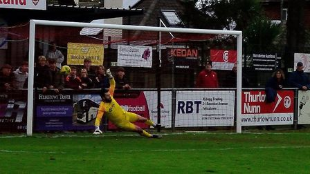 Coggeshall Town keeper Jake Jessup is beaten by Callum Bennett's last minute penalty in a 2-2 draw a