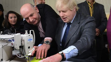 London Mayor Boris Johnson has a go on a sewing machine during a visit to East End Manufacturing. Pi