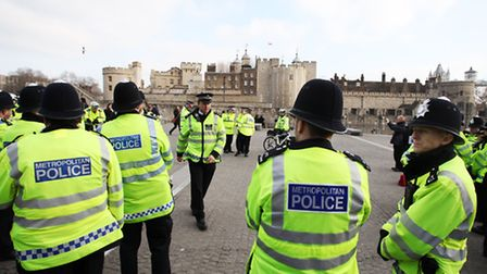 A large group of police officers gather for a meeting at the foot of the Tower of London.