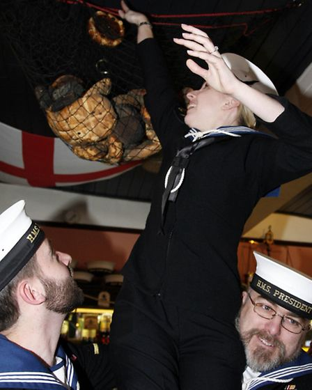Able Seaman Nicola Triggs places this year's hot cross bun above the bar
