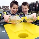 Brothers nine-year-old Jack (left) and Tommy, seven, pour used cooking oil into a recycling bin so i