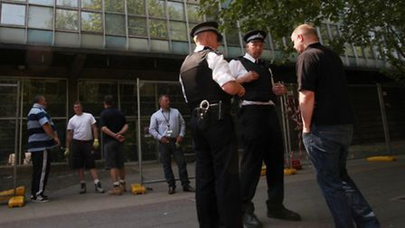 Police watch outside the council block in Cambridge Heath Road, which has been occupied by squatters