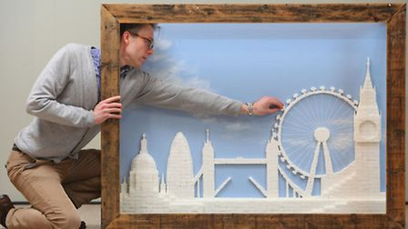 Artist Chris Naylor adds the finishing touches to a model landscape of London made from 2,186 sugar