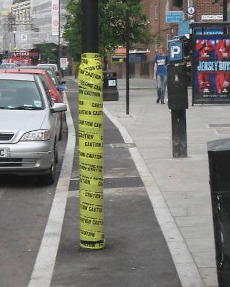 Caution tape wrapped around the lamppost ahead of its removal from the cycle lane