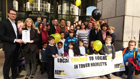 Councillor Joshua Peck,left, supports parents from Chisenhale Primary School as they hand in a petit