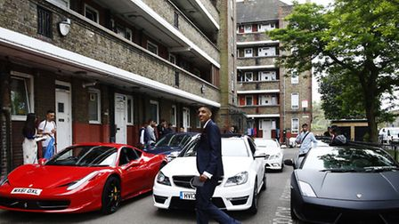 """Aminul Mishu Alam, 16, walks past cars parked at a social housing estate before a parade of """"superca"""