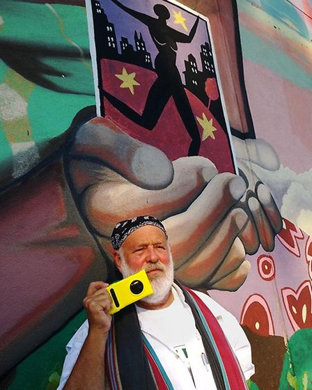 Bruce Weber in front of a mural in Harlem with his smartphone camera.