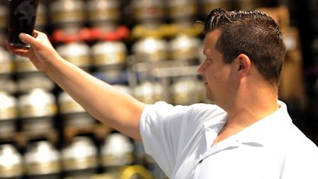 Head brewer Ben Ott checks the quality of the beer