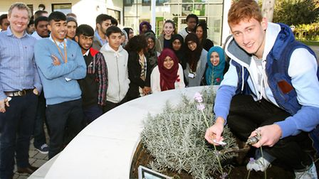 Dylan Farrugia (right) and the A-Level History class plant poppy seeds at Morpeth Secondary
