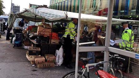 Police carrying out raids at Whitechapel Market. Credit: @damnably